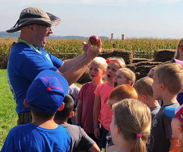 Hugh McPherson teaches a group of school children about the importance of agriculture during a school field trip